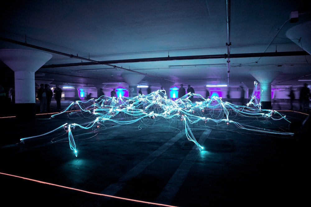 A timelapse image of blue and purple neon lights in a multi-storey car park